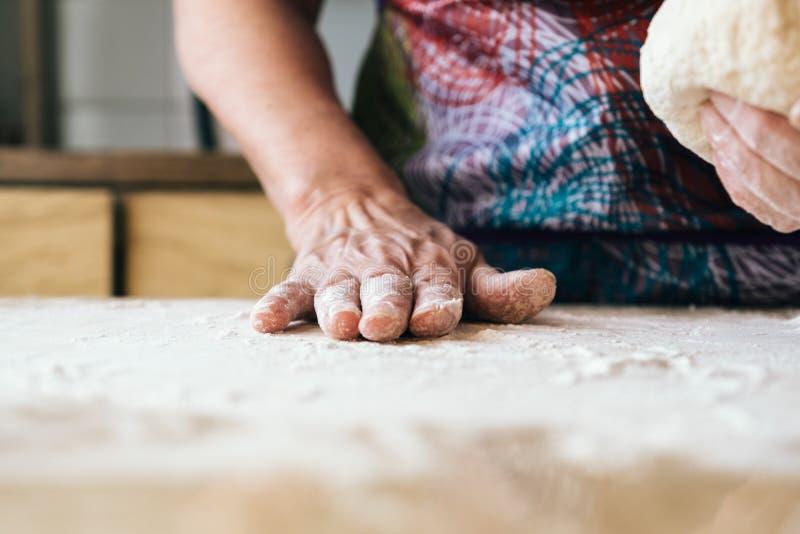 熟练的面包师妇女揉的面团 专业面包店concep 库存照片