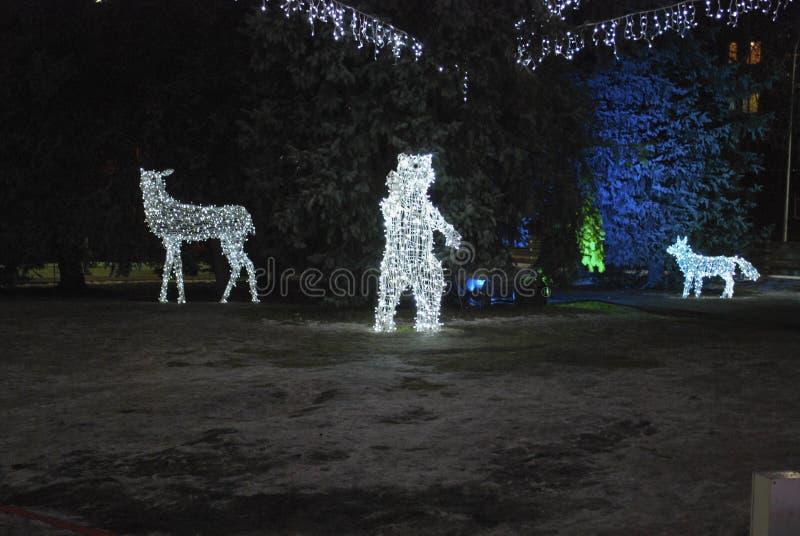 熊、鹿和狐狸从电灯泡 在街道上的圣诞节装饰 图库摄影