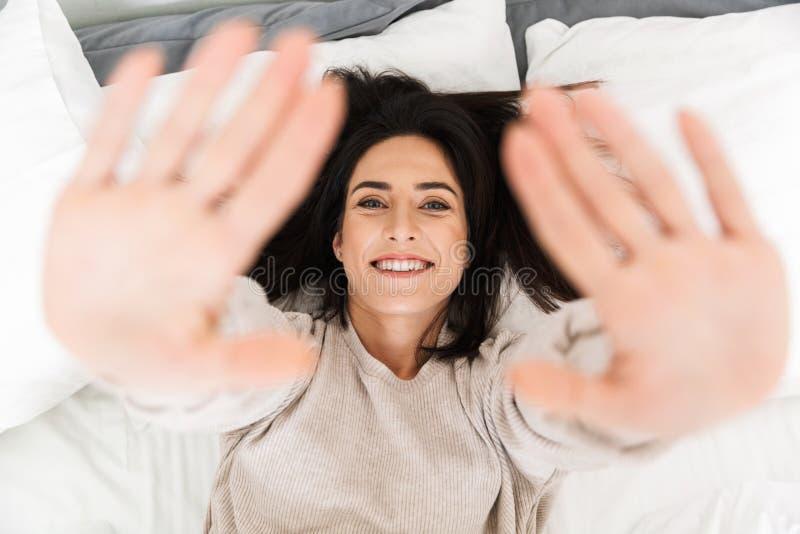 照片从上面愉快的妇女30s,微笑,当在家时在床上 库存照片