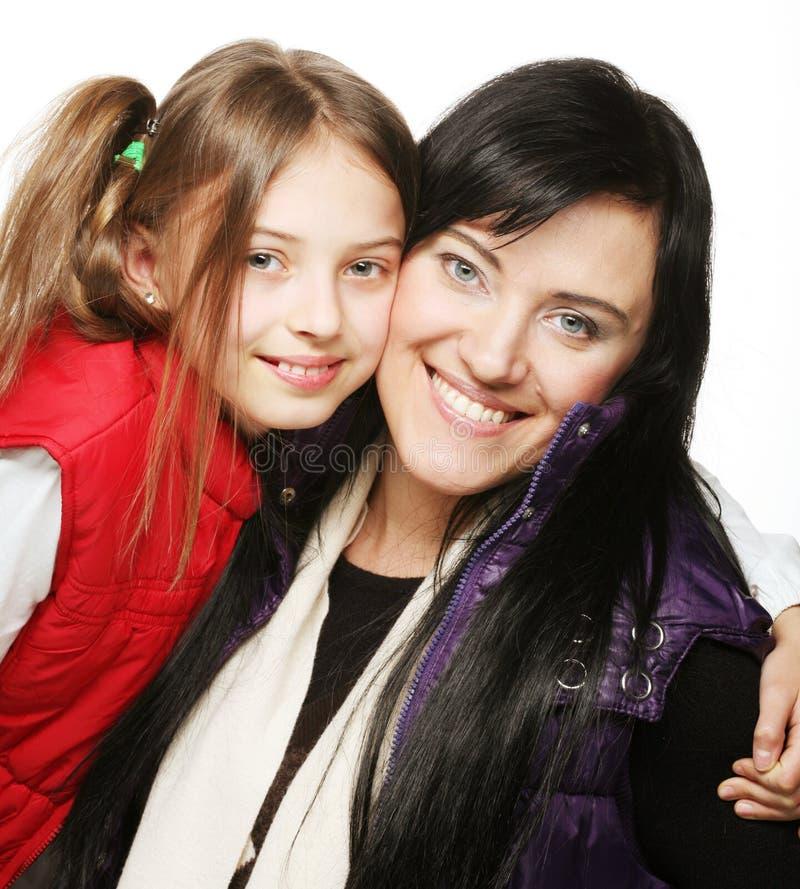 照顾和她的微笑对照相机的女儿 免版税库存图片