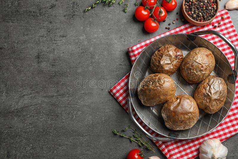 煎锅用在灰色背景,顶视图的鲜美被烘烤的带皮烤的土豆 图库摄影