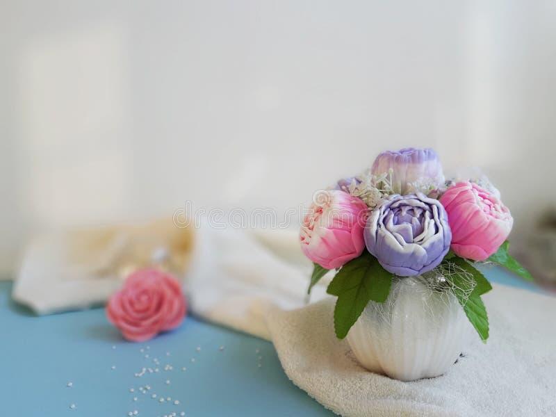 牡丹花束毛巾蓝色表面上的在白色墙壁前面 免版税图库摄影