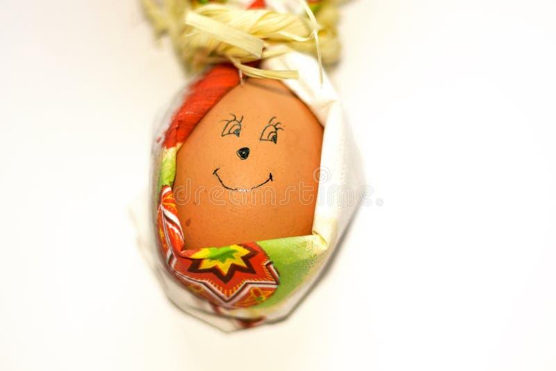 特写镜头与面对的微笑的复活节彩蛋在白色背景隔绝的纸巾兔子形状  春天的准备 免版税库存图片