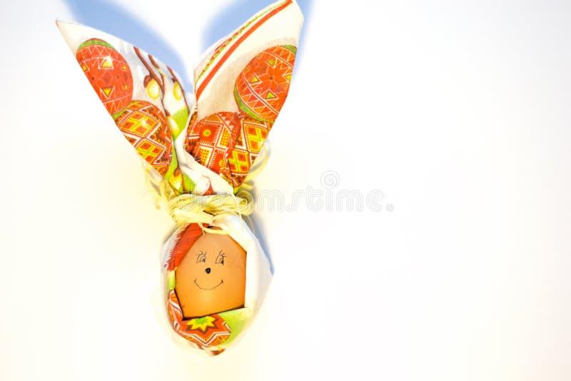 特写镜头与面对的微笑的复活节彩蛋在白色背景隔绝的纸巾兔子形状  春天的准备 库存图片