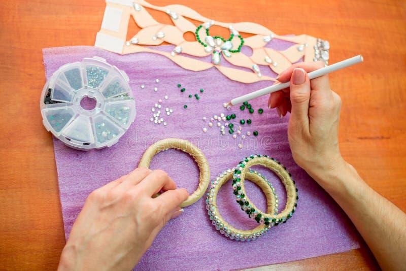 特写镜头妇女的手,装饰有五颜六色的发光的假钻石的镯子 免版税库存照片