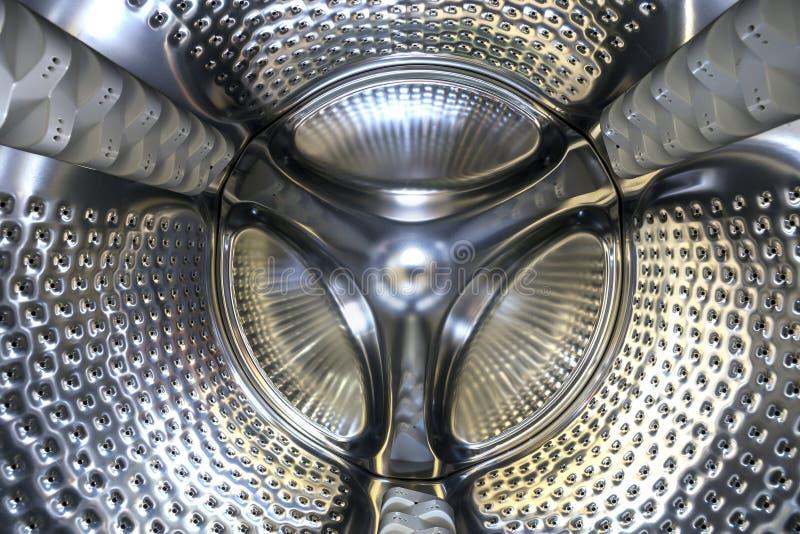 特写镜头细节,现代洗衣机内部不锈的鼓  摘要银色发光的表面设计 免版税图库摄影