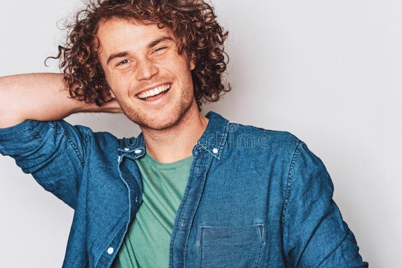 特写镜头英俊的有雀斑的正面微笑的人的演播室图象,摆在为社会广告,隔绝在白色背景 库存照片