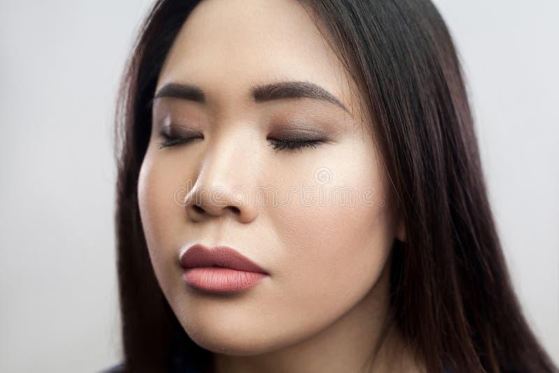特写镜头镇静美丽的深色的亚裔年轻女人秀丽画象有构成的,与闭合的眼睛的平直的黑发身分和 库存图片