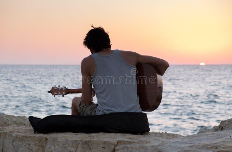 特拉维夫海滩的吉他演奏员在日落 库存图片