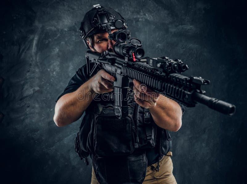 特种部队战士佩带的身体装甲和盔甲与拿着攻击步枪的夜视 反对a的演播室照片 免版税图库摄影