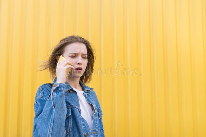 牛仔布夹克的情感女孩用在黄色墙壁的背景的电话讲话 库存照片