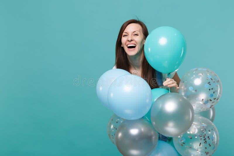 牛仔布衣裳的庆祝和拿着五颜六色的气球的愉快的笑的逗人喜爱的年轻女人画象被隔绝  免版税图库摄影