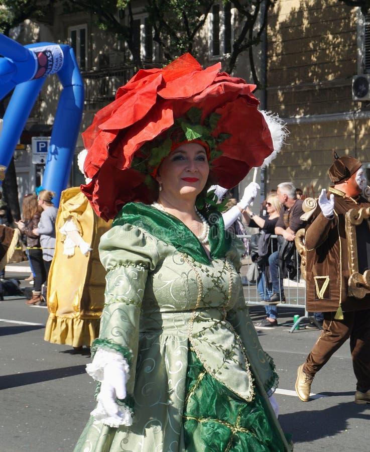 狂欢节服装的妇女有大红色帽子的走在队伍的 免版税库存照片