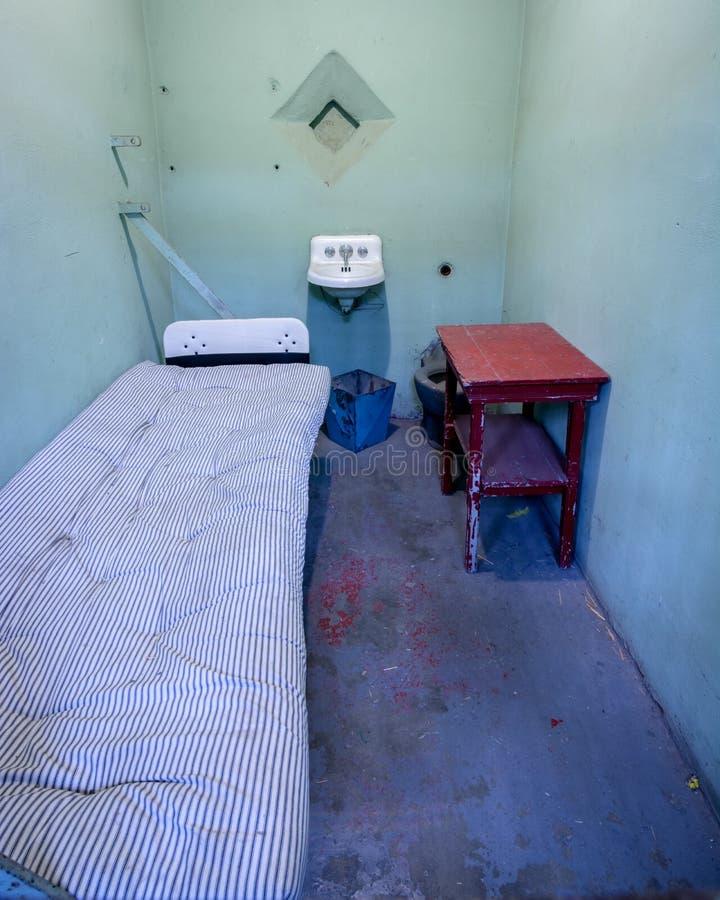 监狱囚犯牢房床和水槽与蓝色被绘的墙壁 免版税库存图片