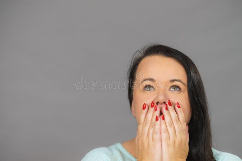 盖她的嘴的羞愧的妇女用手 免版税库存照片