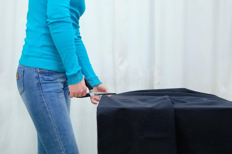 白种人女孩切开在桌上的黑织品 在屋子里 免版税库存图片