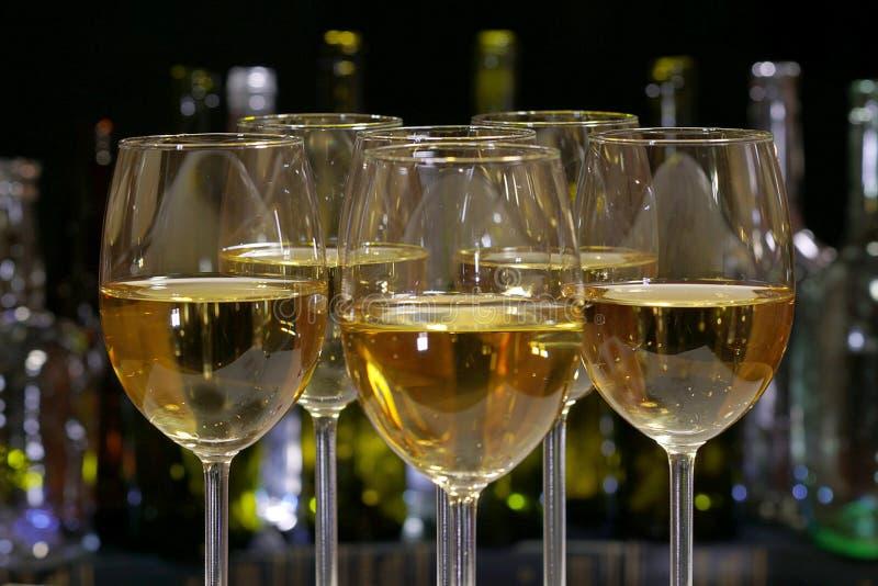 白葡萄酒 与白酒的典雅的酒杯在酒精瓶行的背景  免版税库存照片