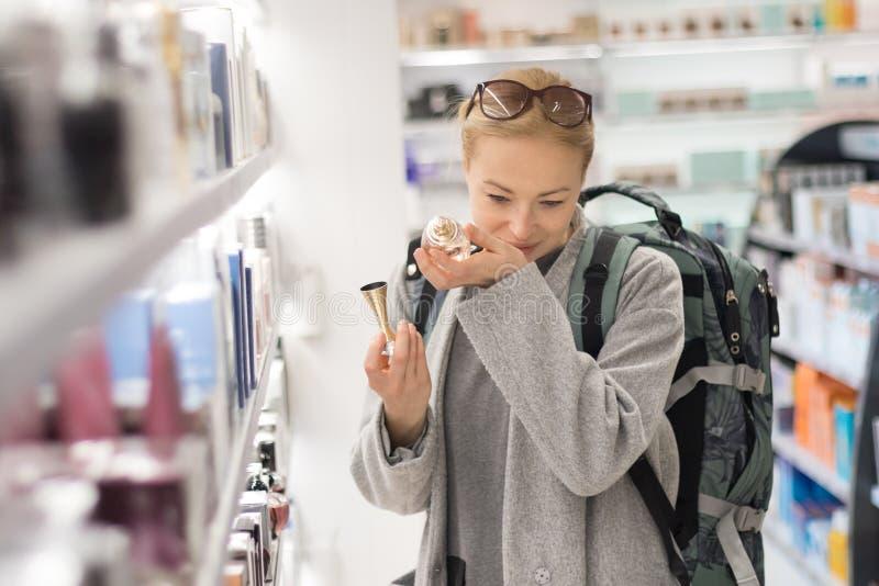 白肤金发的年轻女性选择香水的旅客佩带的旅行背包在机场免税商店 免版税库存照片