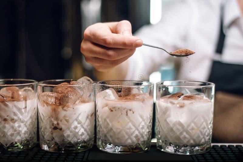 白色俄国鸡尾酒线在酒吧柜台的 男服务员洒可可粉在鸡尾酒 免版税库存照片