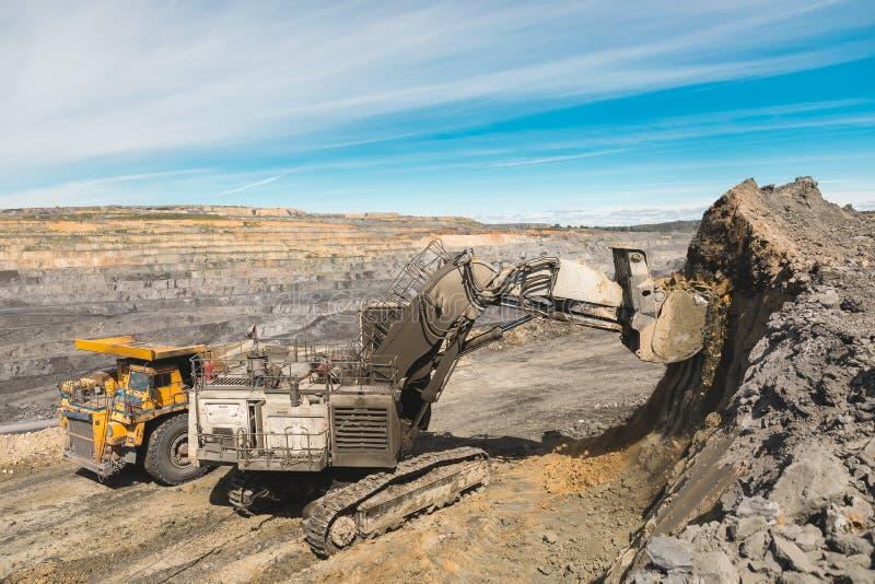 白色大挖掘机在煤矿,用明亮的太阳和好的天空蔚蓝装载品种,在背景 开采 免版税库存图片