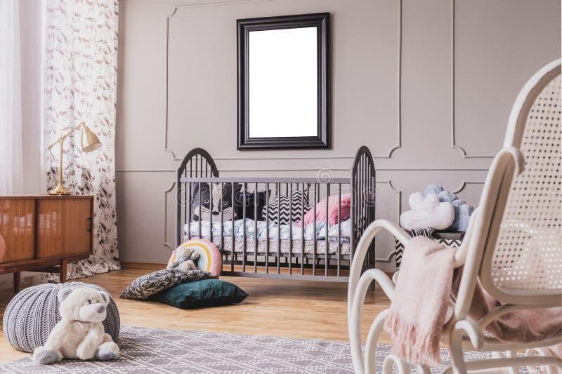 白色女用连杉衬裤涉及时髦的婴孩室内部地板与灰色木小儿床的有枕头、白色摇椅和大模型的 库存图片