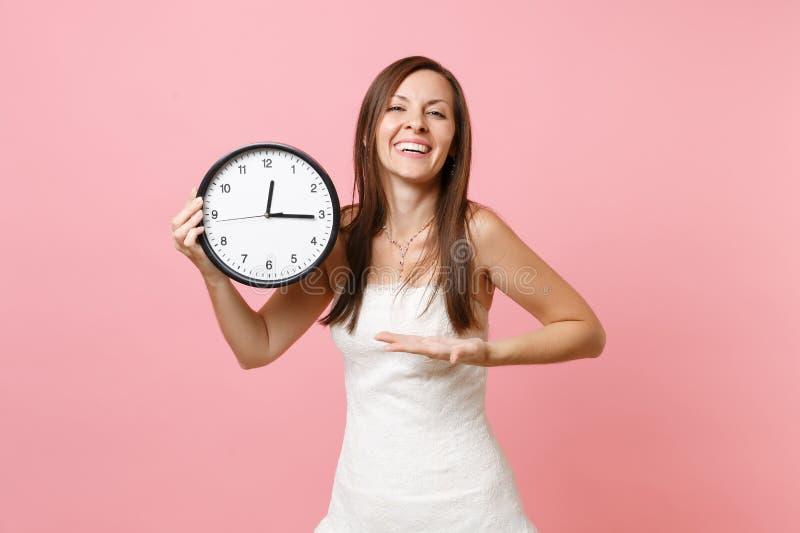 白色婚纱的笑的新娘妇女指向在圆的闹钟的手在粉红彩笔背景 时间 免版税库存照片