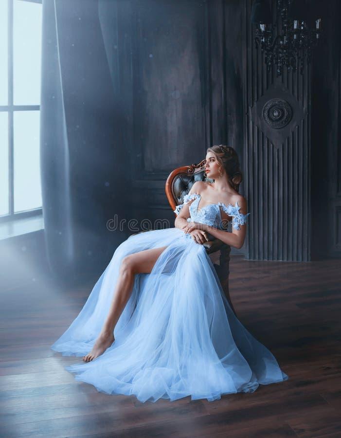 白色别致的东方蓝色礼服疲乏的开会的庄严和骄傲的公主女孩在椅子,夫人显示她苗条 图库摄影