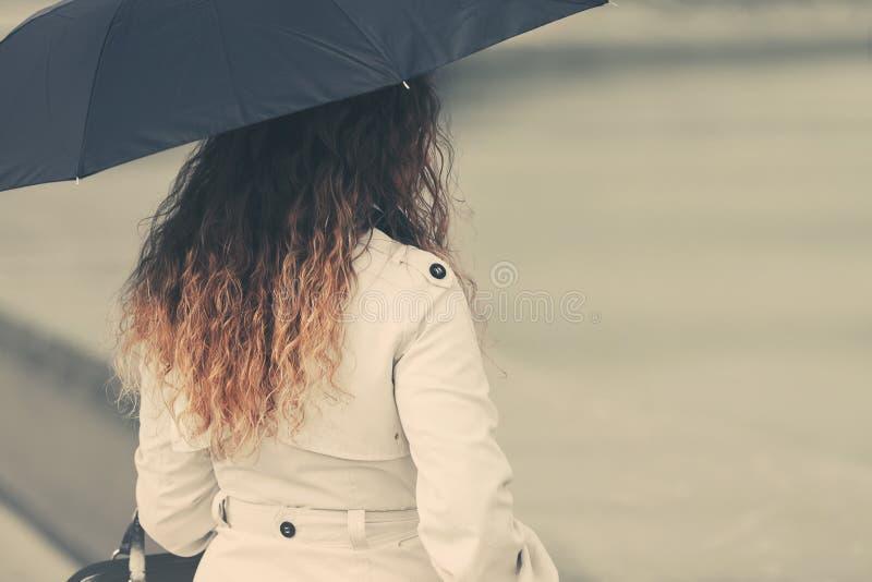 白色军用防水短大衣的时尚妇女有伞的 库存照片