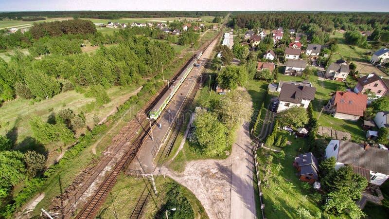 白色和绿色火车在小村庄在Mazovian地区在波兰 免版税图库摄影