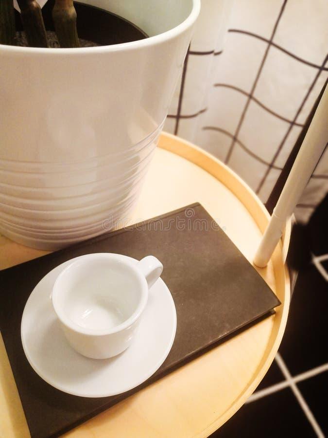 白色杯和白色茶碟在黑名册在咖啡桌上 免版税库存照片