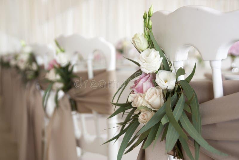 白色椅子用织品和花装饰在婚礼那天 餐馆在假日装饰 库存图片
