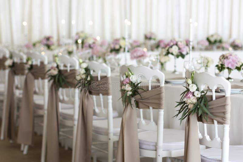 白色椅子用织品和花装饰在婚礼那天 餐馆在假日装饰 免版税库存图片