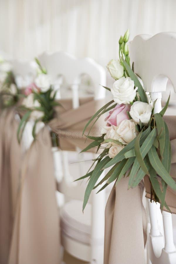 白色椅子用织品和花装饰在婚礼那天 餐馆在假日装饰 库存照片