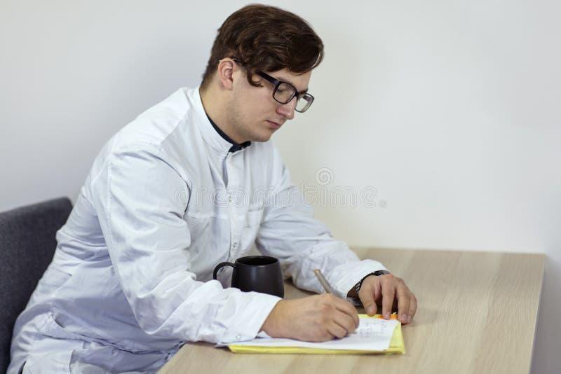 白色成套装备的年轻白种人男性医生写某事坐与茶的桌或咖啡 严肃的面孔expres 免版税库存图片