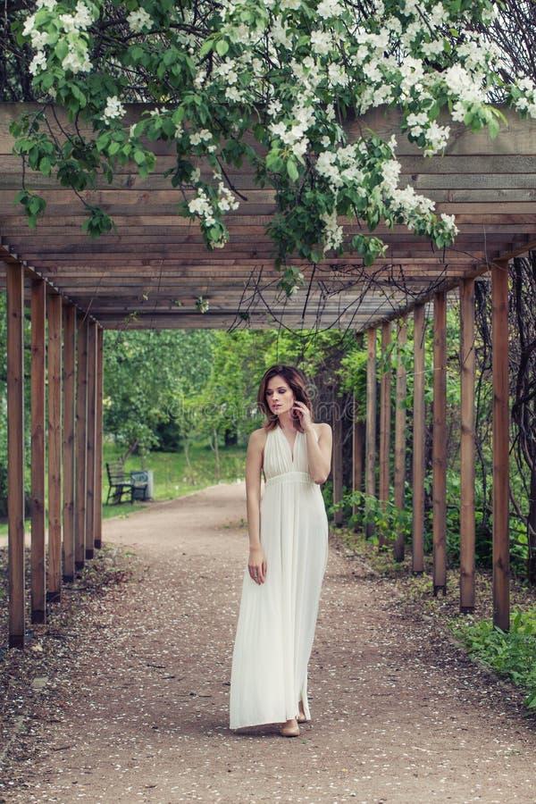 白色礼服户外画象的,浪漫步行完善的春天妇女 免版税库存照片