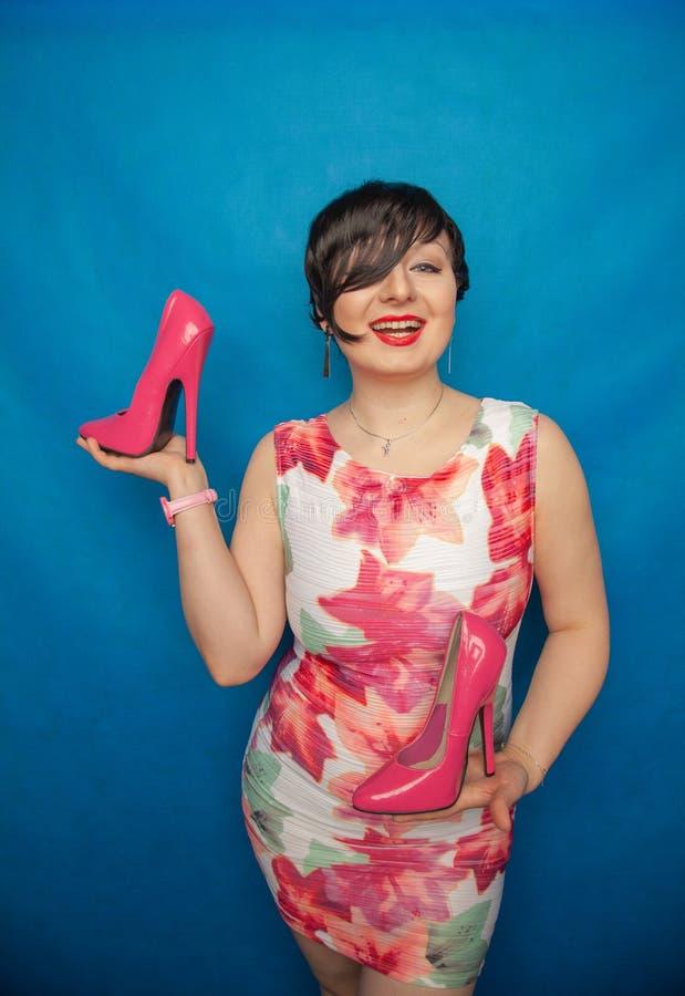 白色礼服的俏丽的白种人妇女有拿着有一只非常高跟鞋的花的一双桃红色鞋子在一蓝色坚实演播室backgrou 库存图片