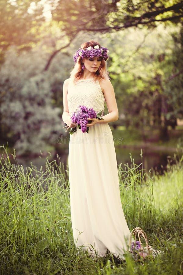白色礼服的年轻女人有花的在户外春天公园 免版税库存图片