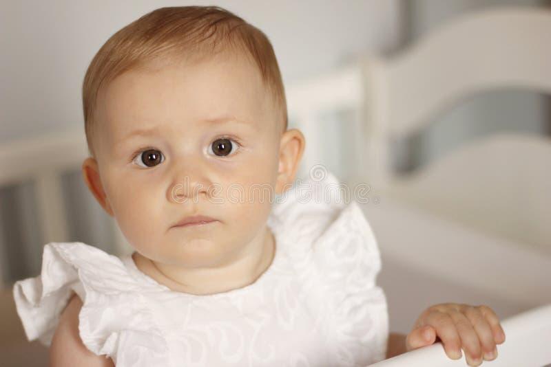 白色礼服身分的可爱宝贝女孩在小儿床 免版税库存图片
