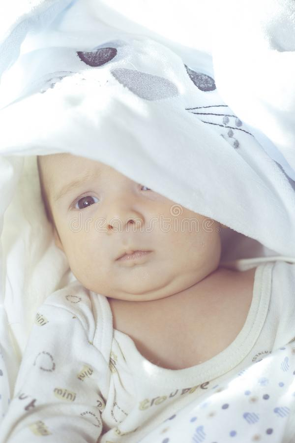 白色背景的可爱的逗人喜爱的新生儿男孩 可爱的孩子穿有长的耳朵的一套兔子服装 复活节节假日 库存图片