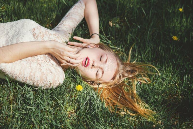 白色鞋带礼服的俏丽的金发碧眼的女人享受在绿草的好日子 免版税库存图片