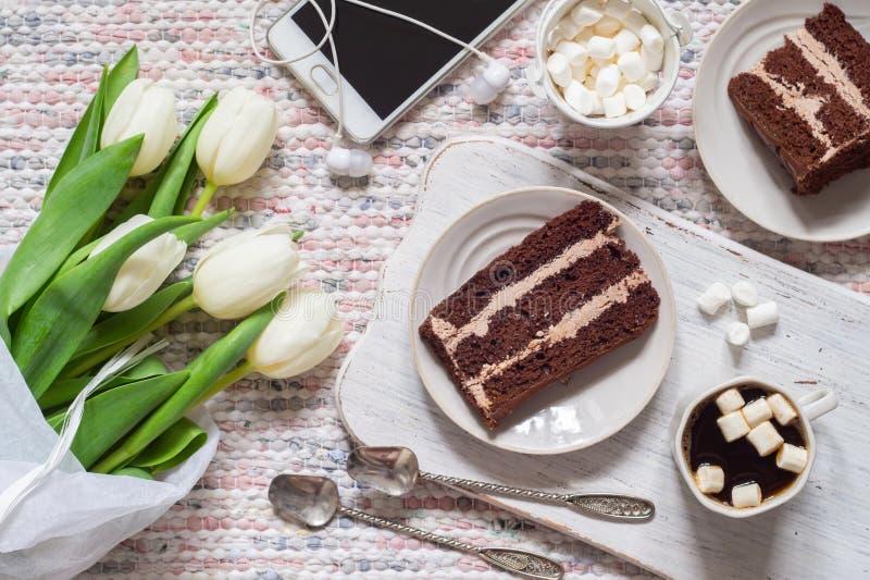 白色郁金香、咖啡和巧克力蛋糕花束  库存图片