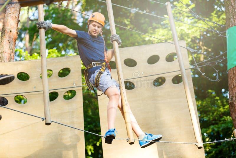 白色T恤杉的运动,年轻,逗人喜爱的男孩在公园在冒险绳索公园盔甲的和安全设备花费他的时间 免版税图库摄影