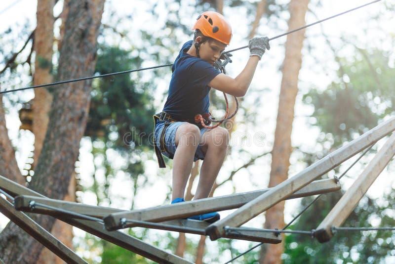 白色T恤杉的运动,年轻,逗人喜爱的男孩在公园在冒险绳索公园盔甲的和安全设备花费他的时间 免版税库存图片