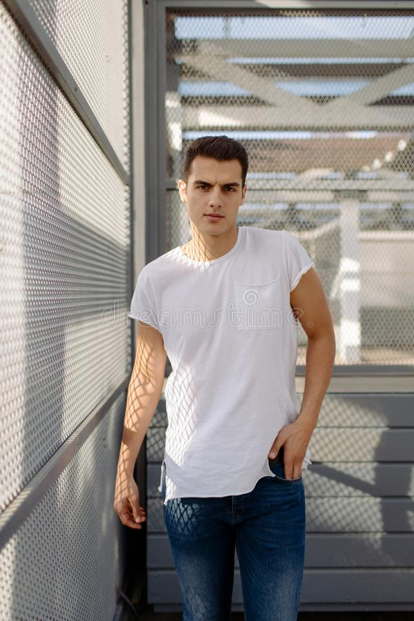 白色T恤的美丽的白种人人和蓝色牛仔裤在街道上停留 免版税图库摄影