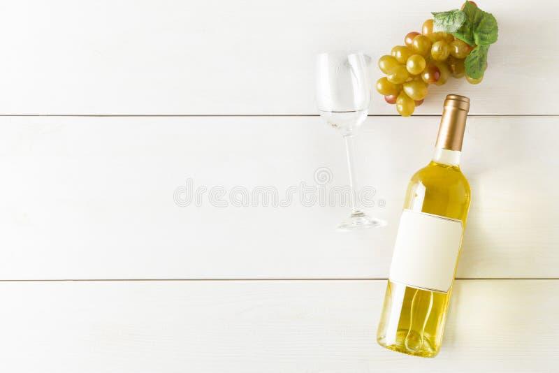 白酒酒瓶用葡萄和酒杯在白色木桌平的位置从上面 免版税库存照片