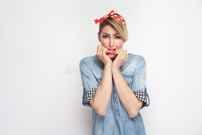紧张的美丽的年轻女人画象偶然蓝色牛仔布衬衣的有看照相机的构成和红色头饰带身分的和 库存照片