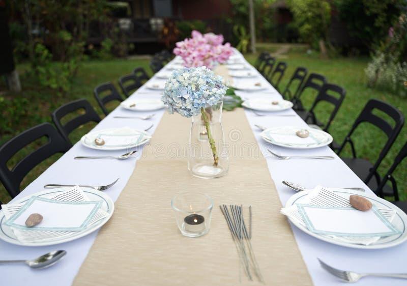 用餐在白色桌板料的集合与室外美丽的花束的花 图库摄影
