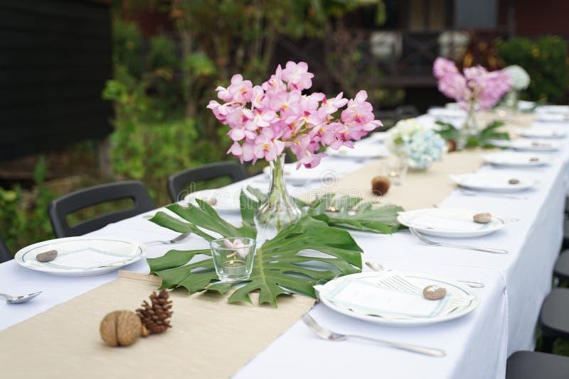 用餐在白色桌板料的集合与室外美丽的花束的花 免版税库存图片