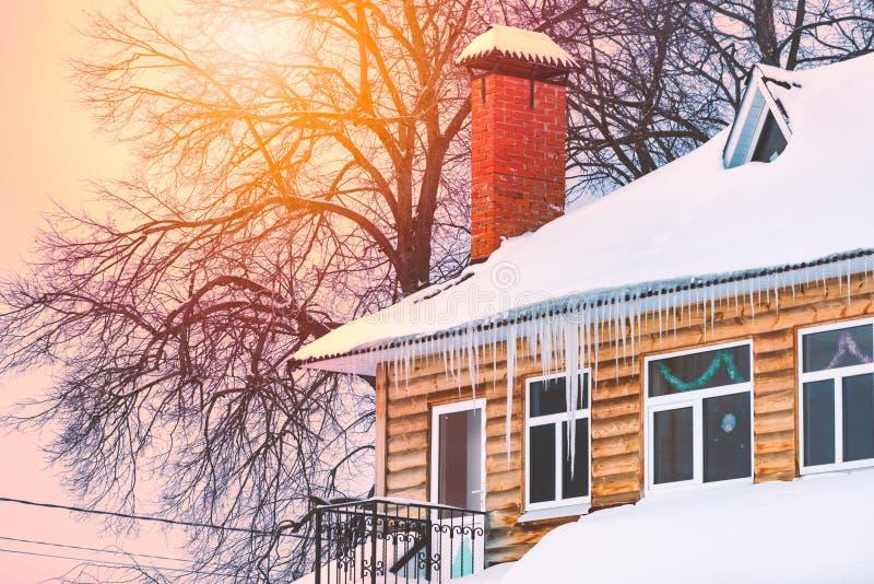 用雪和冰柱盖的木房子 免版税库存照片