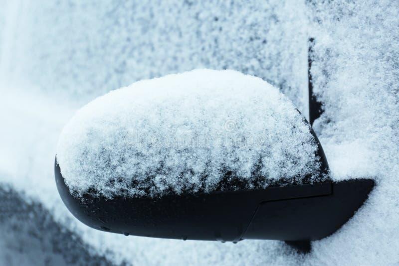 用雪盖的汽车后视镜 免版税库存照片